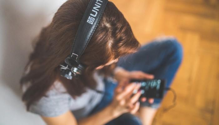 Nainen kuuntelee musiikkia matkapuhelimella
