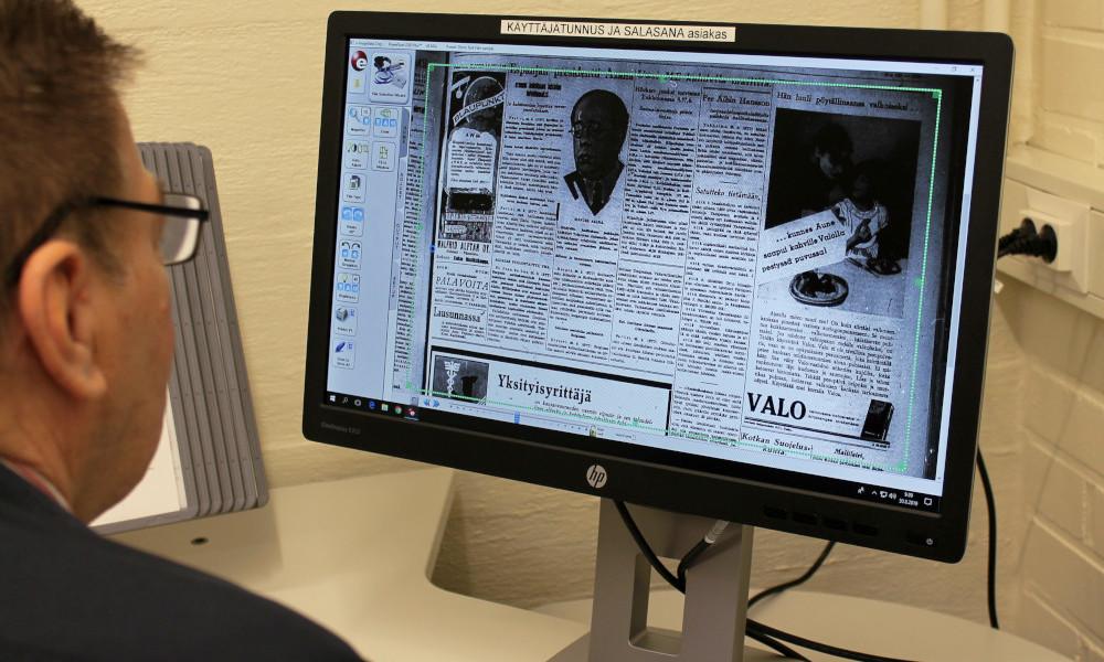 Mies lukee mikrofilmiä tietokoneen näytöltä