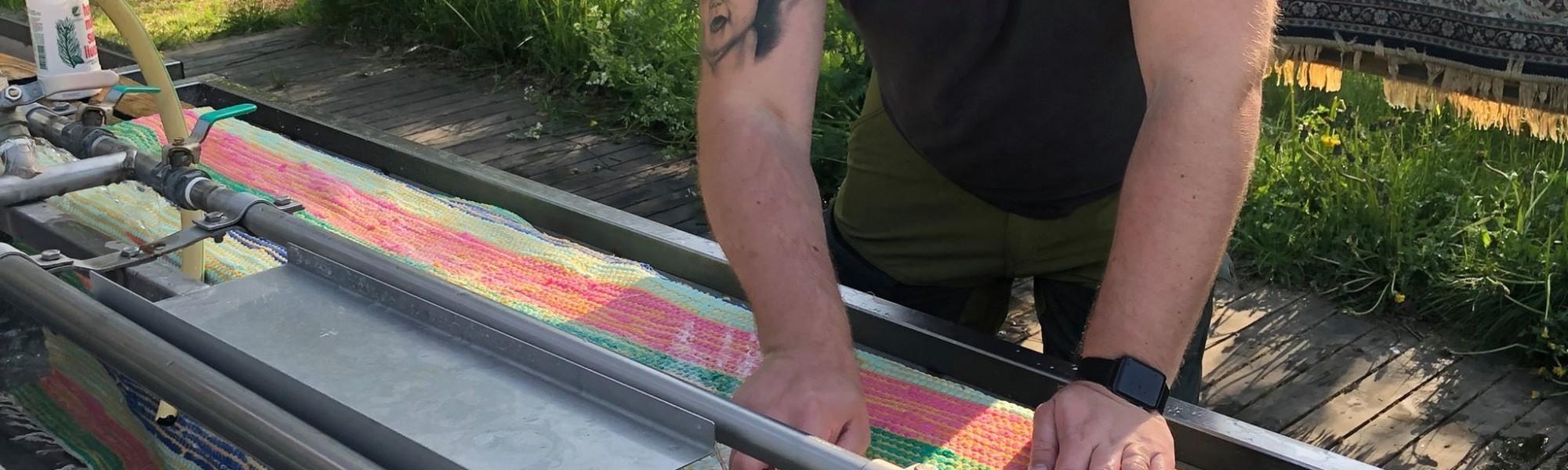 Mies pesemässä mattoja