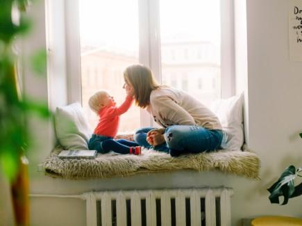 Kuvassa vauva koskettaa äidin naamaa, istuvat ikkunalaudalla