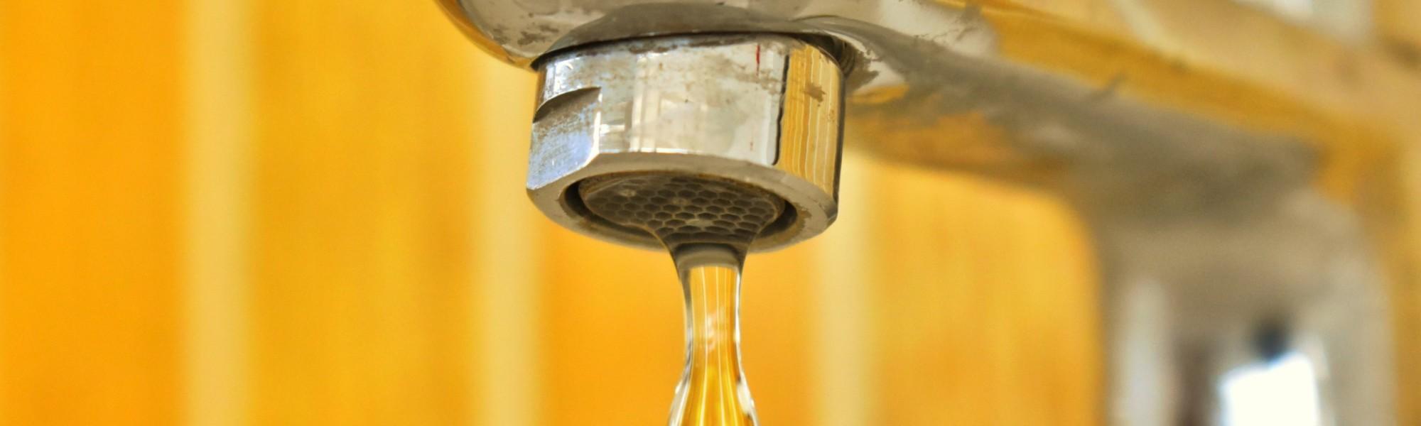 Vesihanasta valuu vettä, kirkkaan keltainen tausta