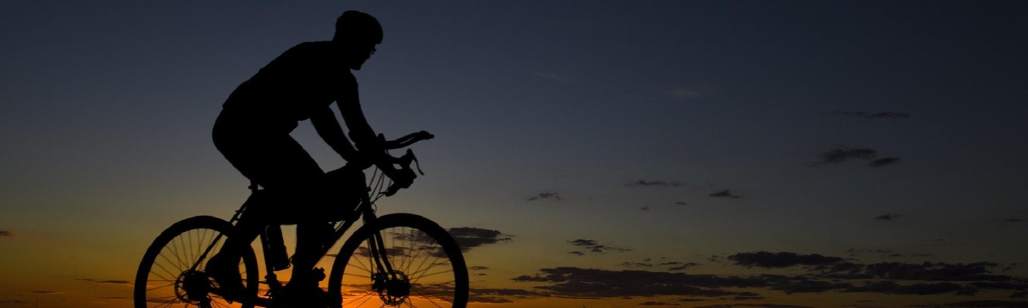 Mies ajaa pyörällä illansuussa