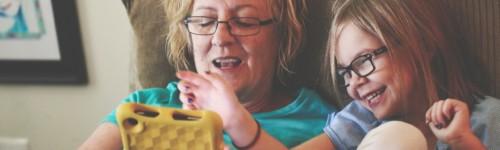 Isoäiti ja lapsi nauravat sohvalla, selaavat tablettia