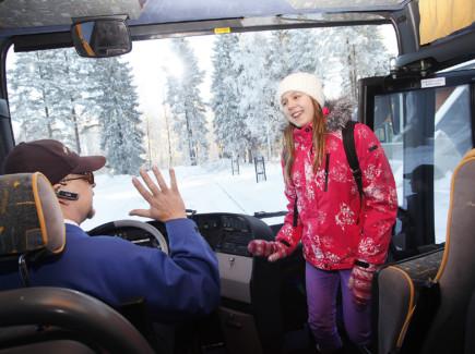 Bussinkuljettaja tervehtii nuorta matkustajaa