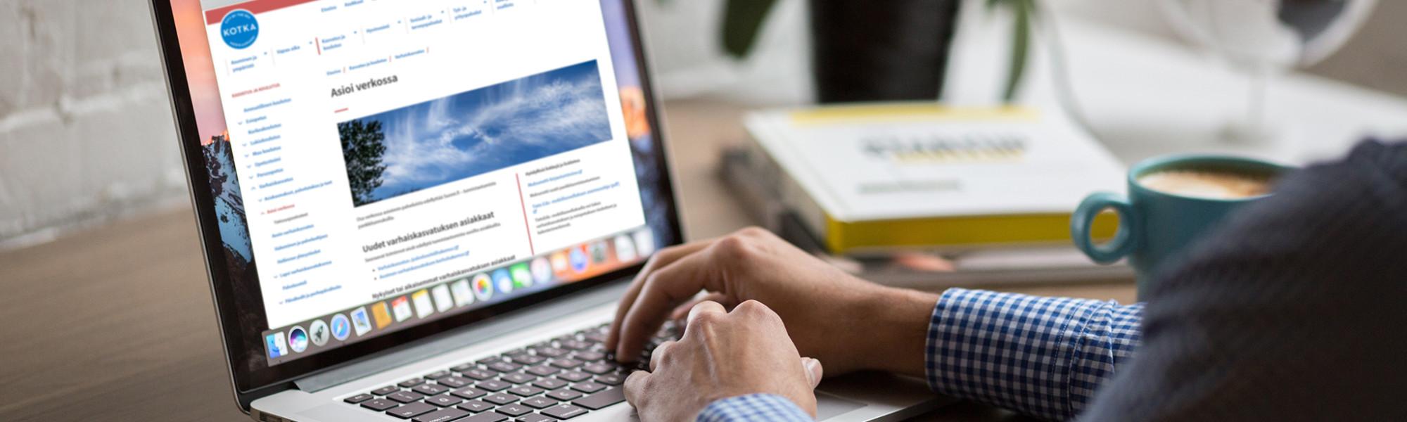 Kuvassa henkilö selaa verkkosivustoa tietokoneella