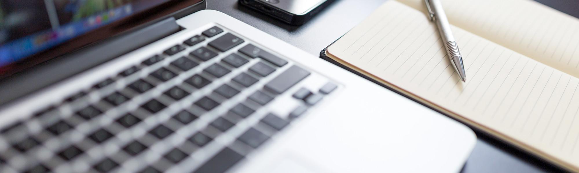 Kuvassa tietokone, puhelin, muistilehtiö sekä kynä