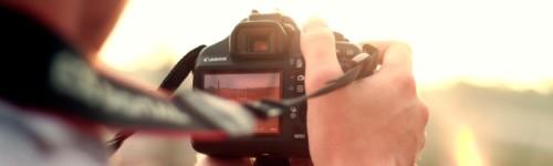 Kuvassa ihminen pitelee kameraa, jolla ottaa kuvaa