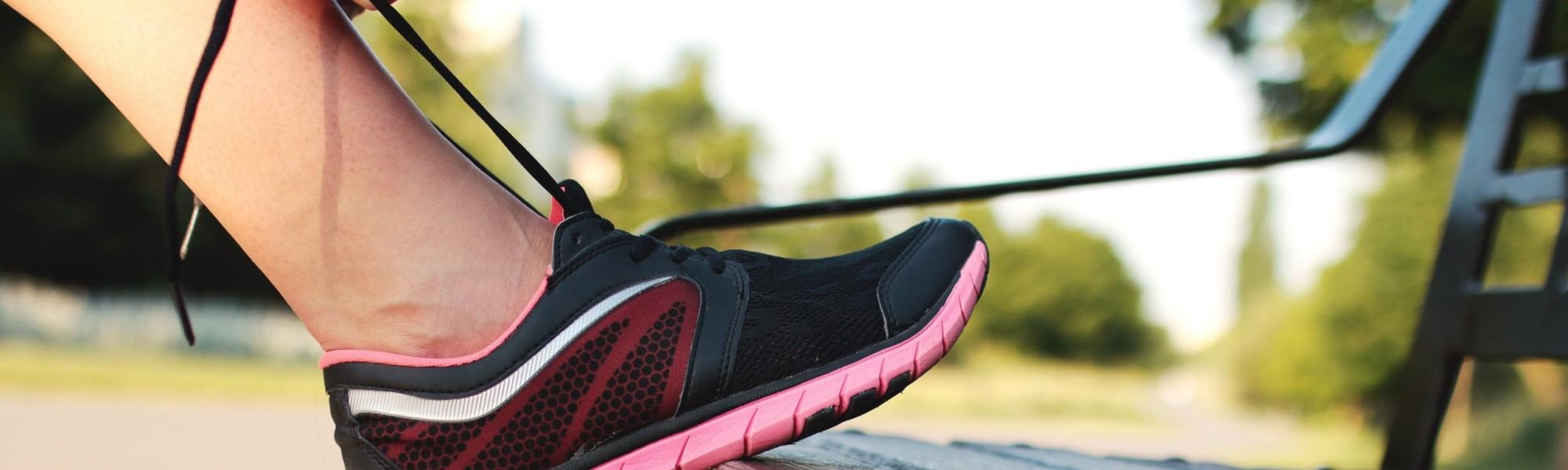 Kuvassa jalka nostettu penkille, kädet sitovat kengännauhoja