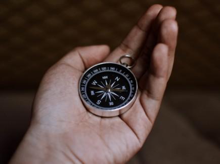 Kuvassa kompassi ihmisen kädessä