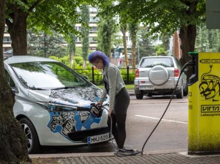 Nainen lataa Kotkan kaupungin sähköautoa Sibeliuksenpuiston parkkipaikalla