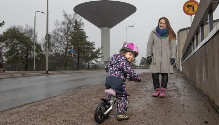 Kuvassa tyttö potkupyörällä naisen kanssa, Karhulan vesitornin edessä