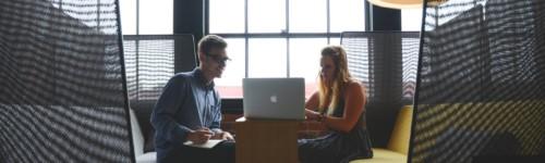Kuvassa mies ja nainen istuvat vastakkain sohvaryhmällä, katsovat tietokonetta
