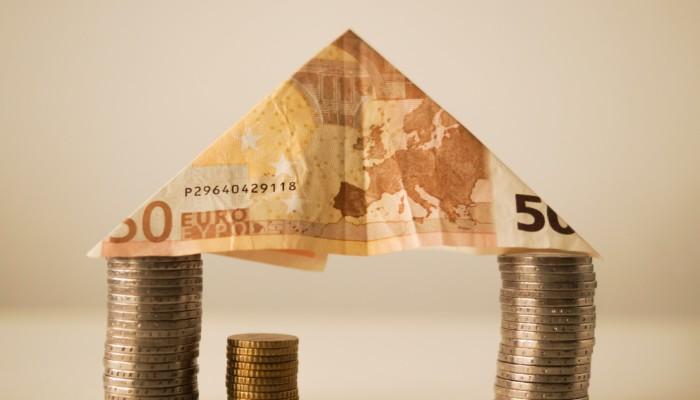 Kuvassa pino kolikkoja, joiden päällä taiteltu 50 euron seteli, muodostavat talon muotoisen rakennelman