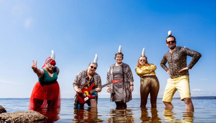 Kuvassa Diskohai bändin jäsenet, viisi aikuista matalassa vedessä