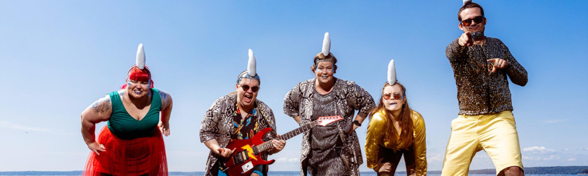Kuvassa Diskohai yhtyeen viisi jäsentä, joilla päässään leikkihain evä ja he seisovat matalassa vedessä