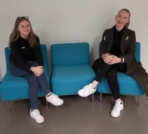 Kuvassa Emma Saarelainen ja Oliva Lahtinen istuvat sinisillä tuoleilla.