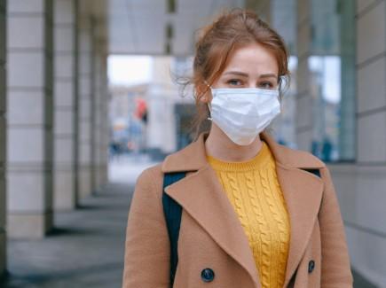 Kuvassa nuori nainen, jolla päällä kertakäyttöinen maski