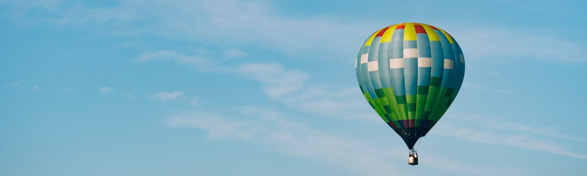 Kuvassa on värikäs kuumailmapallo sinisellä taivaalla.