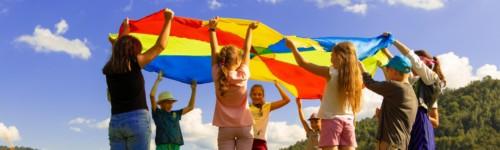 Kuvassa lapset pitelevät välissään isoa ja värikästä kangasta kesäisesellä nurmikolla.