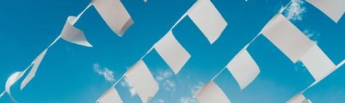 Kuvassa liehuu sinistä taistasta vasten paljon pieniä valkoisia lippuja.