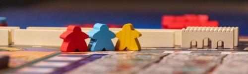 Kuvassa näkyy lautapeli ja kolme eri väristä ihmishahmoista pelinappulaa.