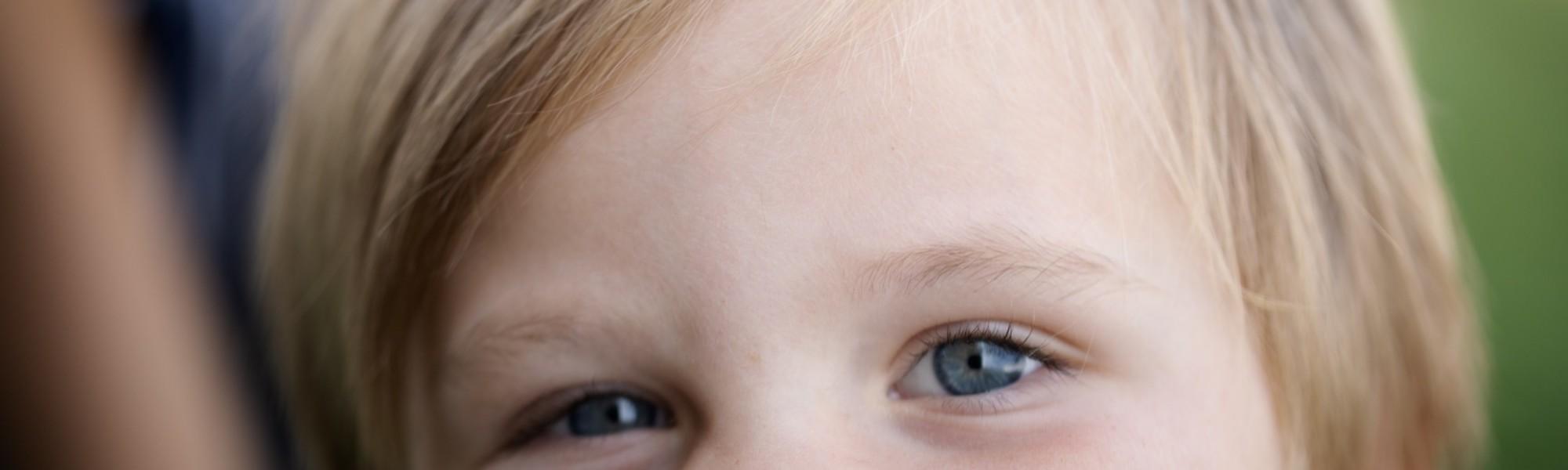 Kuvassa näkyy pienen lapsen kasvojen yläosa, eli silmät ja hiukset.