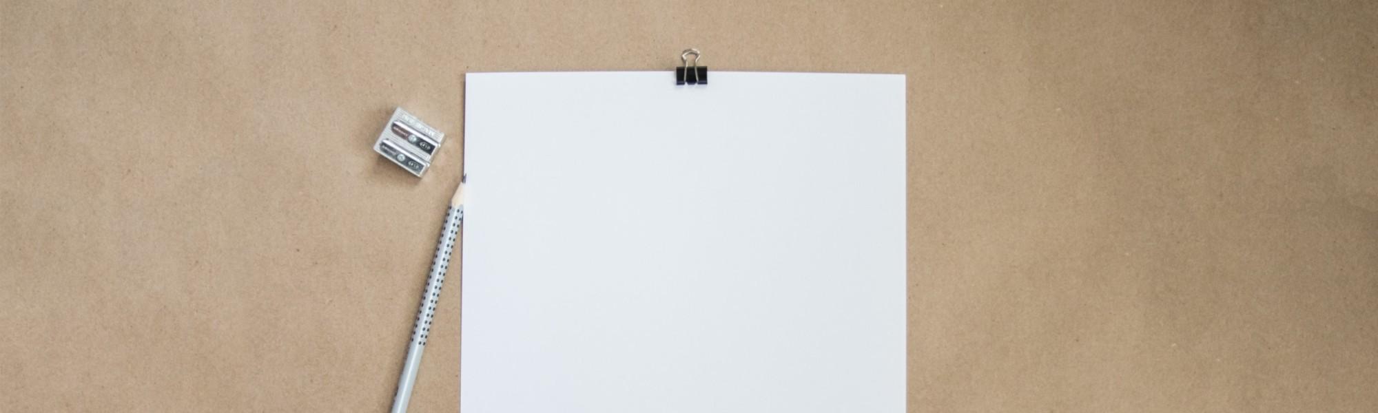 Kuvassa on tyhjä paperiarkki, kynä ja terotin.