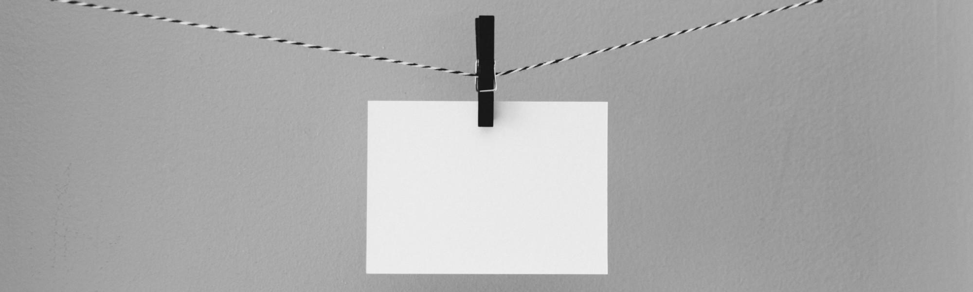 Kuvassa on narulle pyykkipojalla ripustettu tyhjä paperiarkki.