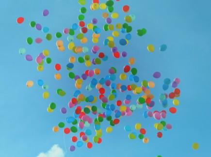 Kuvassa on paljon värikkäitä ilmapalloja sinisellä taivaalla.