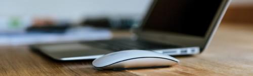 Kuvassa on kannettava tietokone ja hiiri pöydällä.