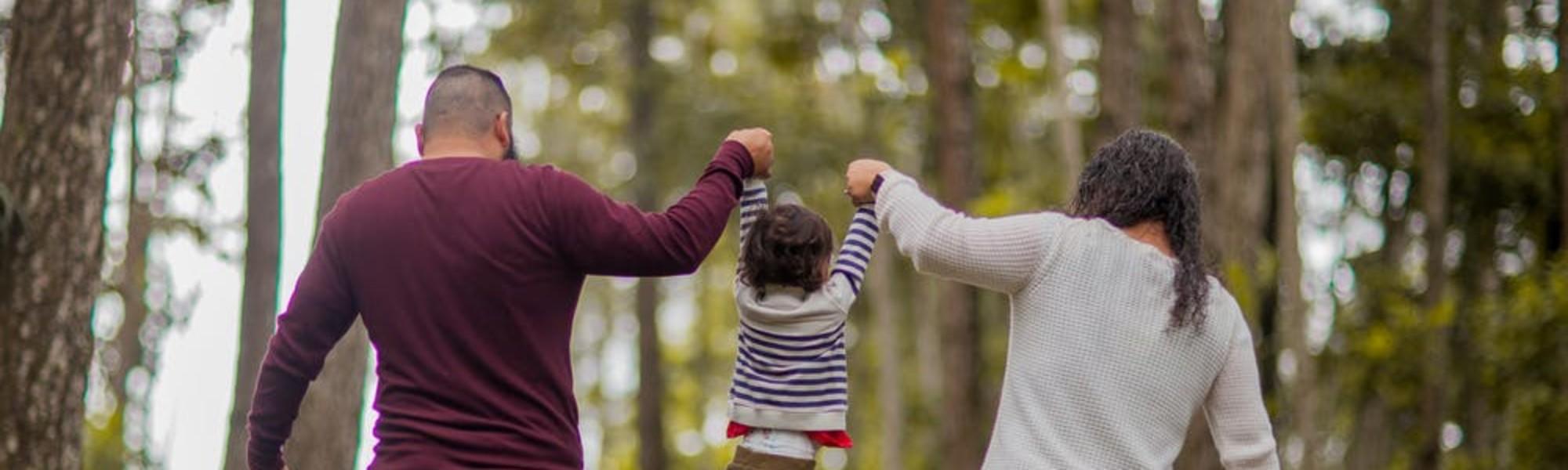 Kuvassa on takaa päin kuvattuna isä ja äiti, jotka pitävät kädestä välissään olevaa lasta.