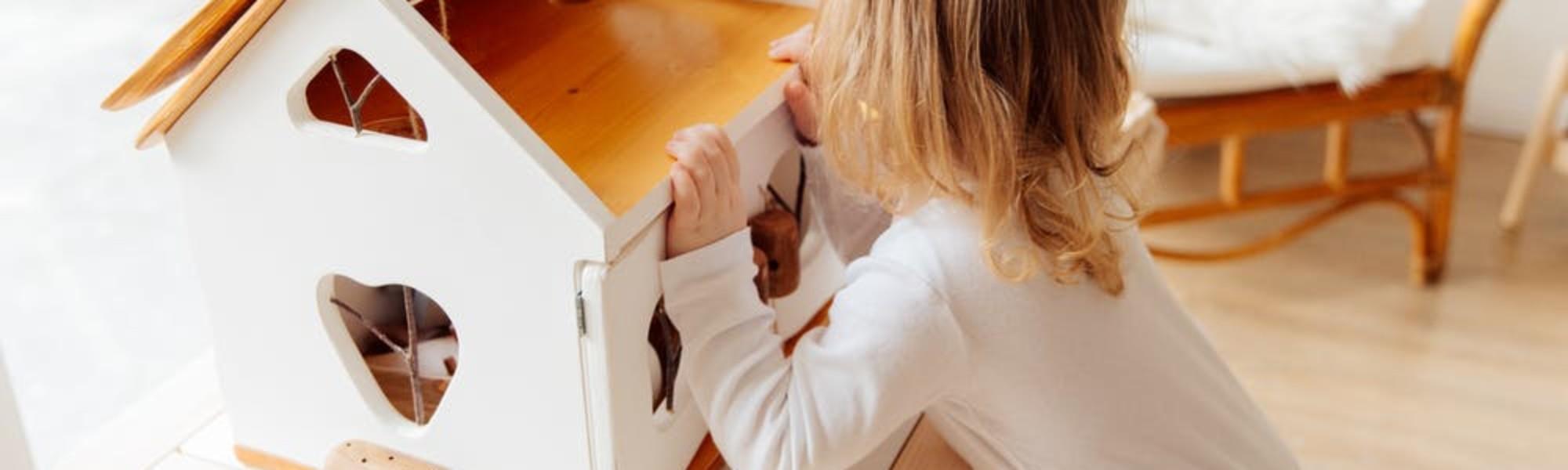 Kuvassa pieni lapsi leikkii nukkekodilla.