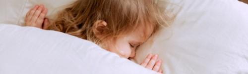 Kuvassa näkyy peiton alla nukkuvan lapsen pää tyynyllä.