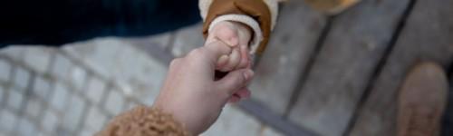 Kuvassa näkyy aikuisen käsi pitelemässä lapsen kättä.