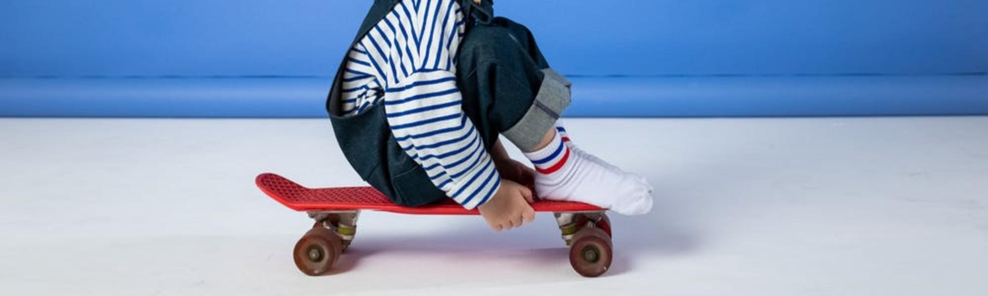 Kuvassa lapsi istuu skeittilaudan päällä.