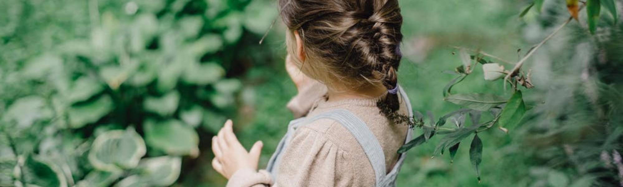 Kuvassa on lettipäinen tyttö vihreässä pihapiirissä.