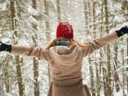 Nainen kädet levällään lumisessa metsässä, selkäpuolelta kuvattuna.