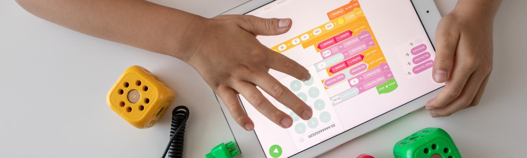 Kuvassa näkyy tablettitietokone ja kädet.