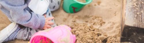 Kuvassa lapsi istuu ämpäreitä ympärillään hiekkalaatikollla.