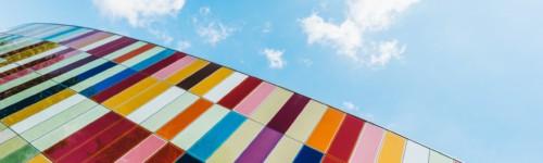 Kuvassa näkyy värikäs rakennuksen seinä sinistä taivasta vasten.