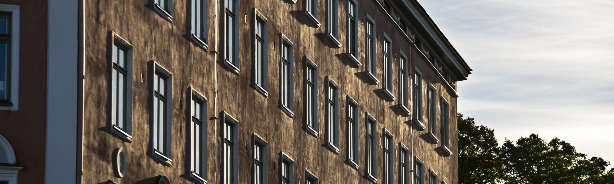 Kuvassa on kerrostalon seinä ja ikkunat