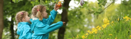 Kuvassa kaksi lasta poimii puuhub ripustettuja pääsiäismunia.