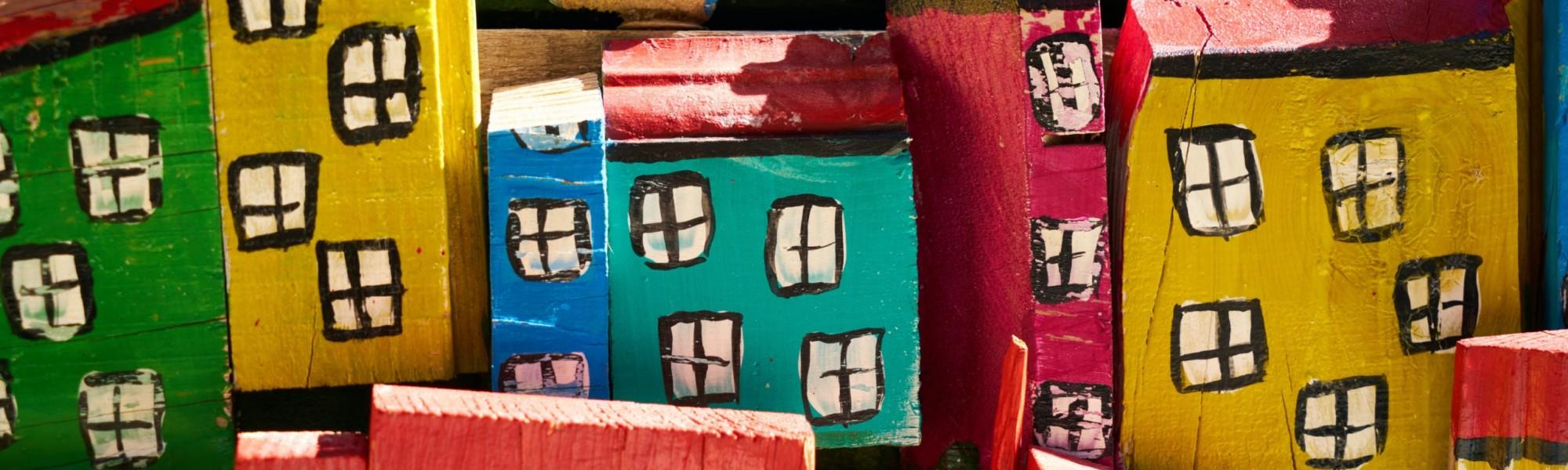 Kuvassa on eri värisiä puisia palikkataloja.