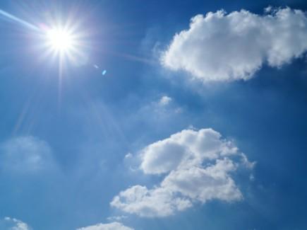 Kuvassa on sininen taivas, pilvenhattaroita ja aurinko.