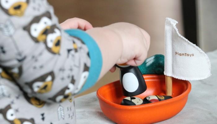 Kuvassa lapsi leikkii pienellä leluveneellä.