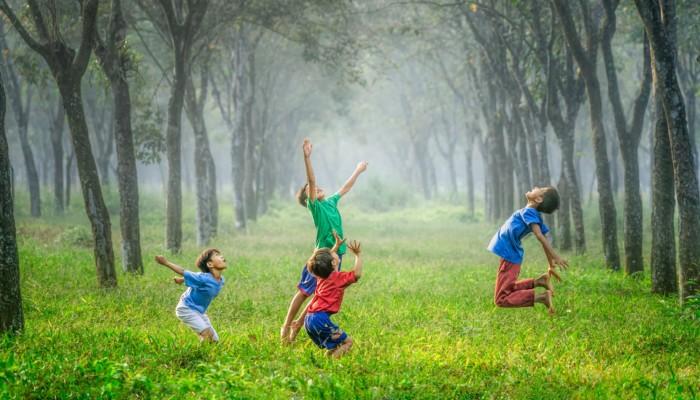 Kuvassa on neljä ilmaan hyppäävää iloista lasta vihreän luonnon keskellä.