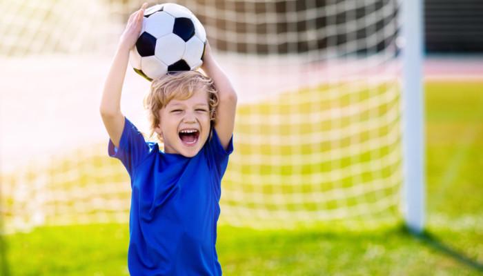 Iloinen poika pitää jalkapalloa päänsä yläpolella, takana näkyy jalkapallomaali