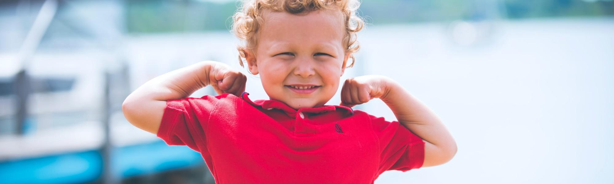 Kuvassa pieni kikkarahiuksinen ja punapaitainen poika pullistelee hauislihaksia ja esittää kuinka vahva hän on.