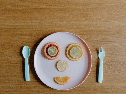 Kuvassa on valkoinen lautanen puupöydällä. Lautaselle on tehty leikatuista sitrushedelmistä iloiset kasvot.
