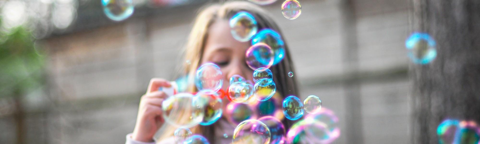 Kuvassa pieni tyttö puhaltaa paljon värikkäitä saippuakuplia.